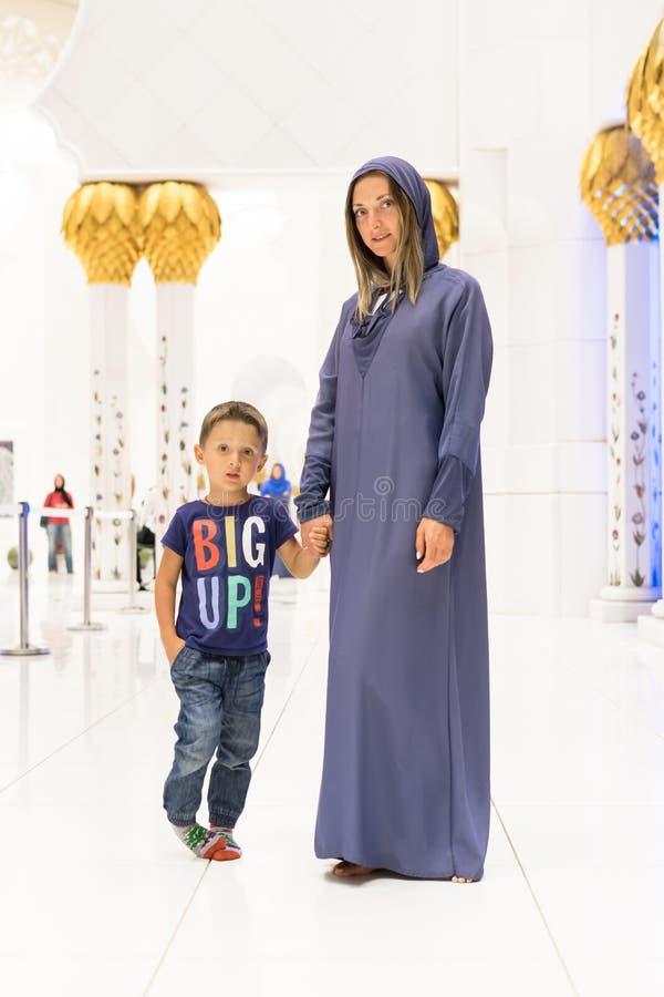 Vrouw met het leuke zoon dromen bij de grote moskee van Sheikh Zayed Mosque in Abu Dhabi die abaya, paranja in nacht dragen Trave royalty-vrije stock afbeelding