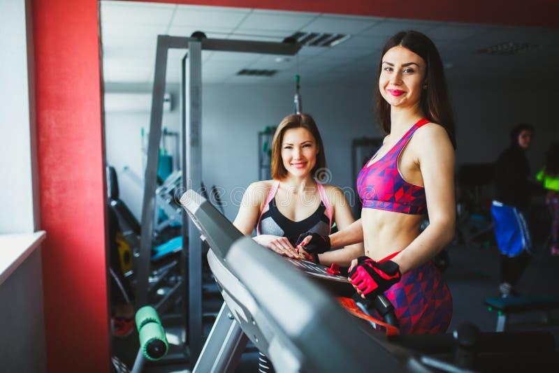 Vrouw met het persoonlijke trainer uitoefenen op tredmolen in gymnastiek royalty-vrije stock afbeeldingen