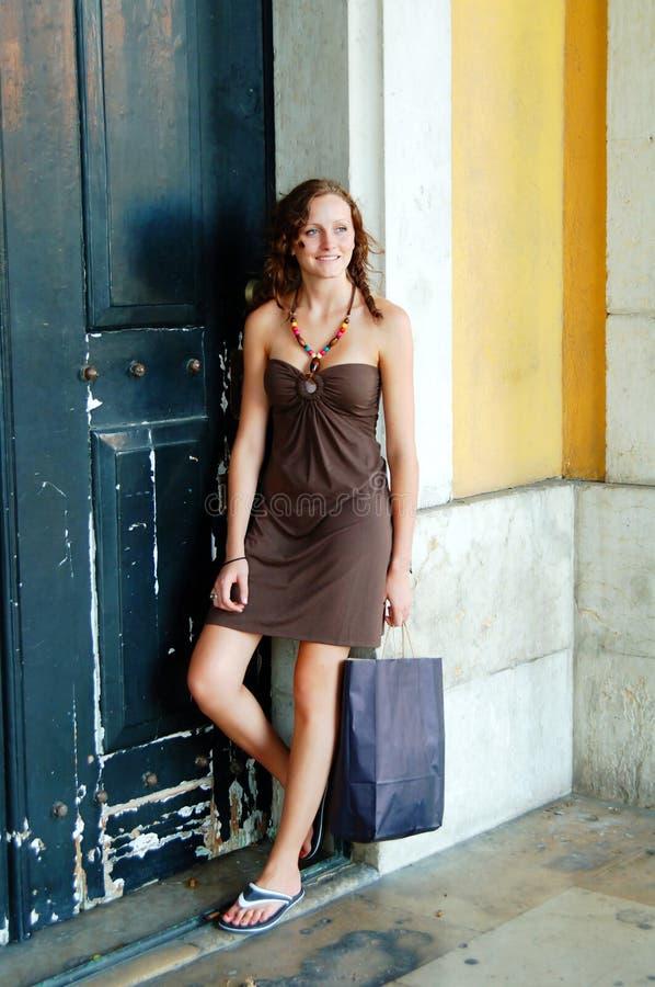 Vrouw met het shoping van zak in oude deuropening stock afbeeldingen