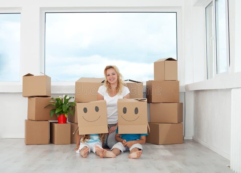 Vrouw met het spelen jonge geitjes in hun nieuw huis stock foto's
