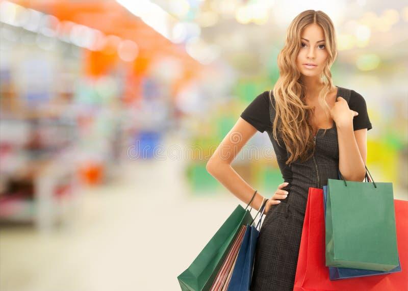 Vrouw met het winkelen zakken bij opslag of supermarkt stock afbeelding