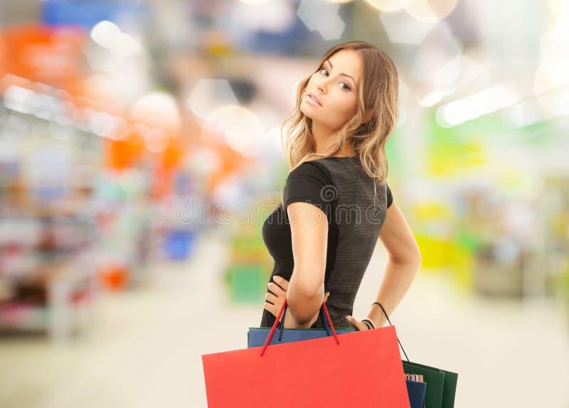 Vrouw met het winkelen zakken bij opslag of supermarkt royalty-vrije stock foto's