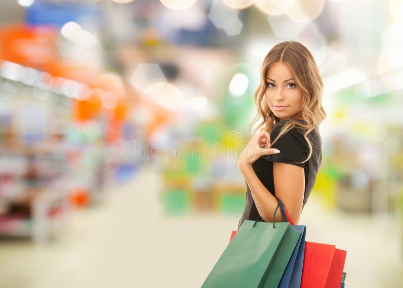 Vrouw met het winkelen zakken bij opslag of supermarkt stock fotografie