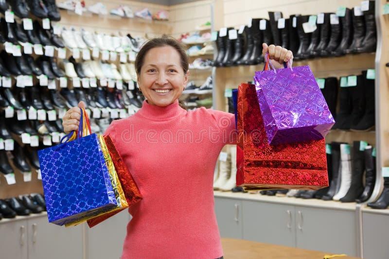 Vrouw met het winkelen zakken bij schoenenwinkel stock foto's