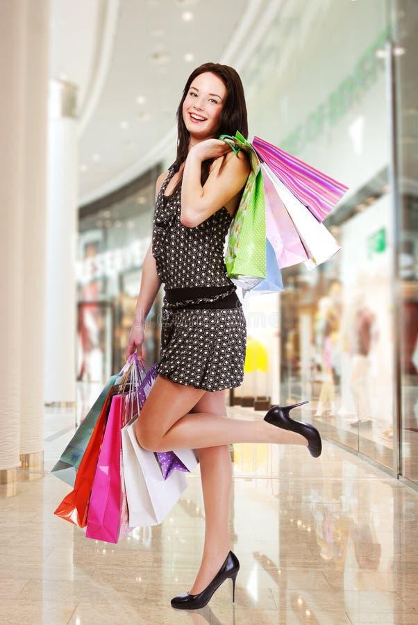 Vrouw met het winkelen zakken bij winkel stock foto