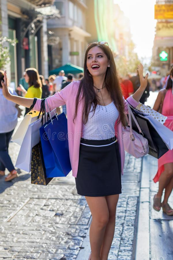 Vrouw met het winkelen zakken in een bezige stadsstraat stock afbeelding