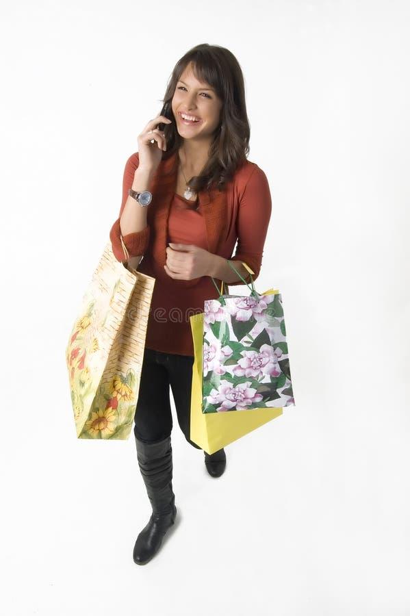 Vrouw met het winkelen zakken en cellulaire telefoon royalty-vrije stock afbeeldingen
