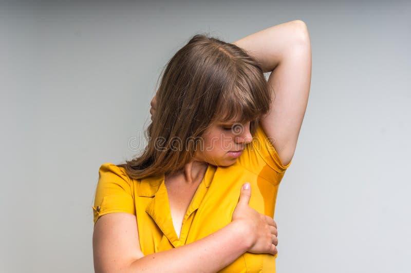 Vrouw met het zweten onder oksel in gele kleding royalty-vrije stock fotografie