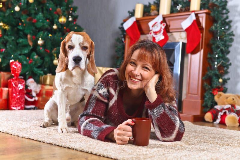 Vrouw met hond in de ruimte met Kerstmisdecoratie royalty-vrije stock foto