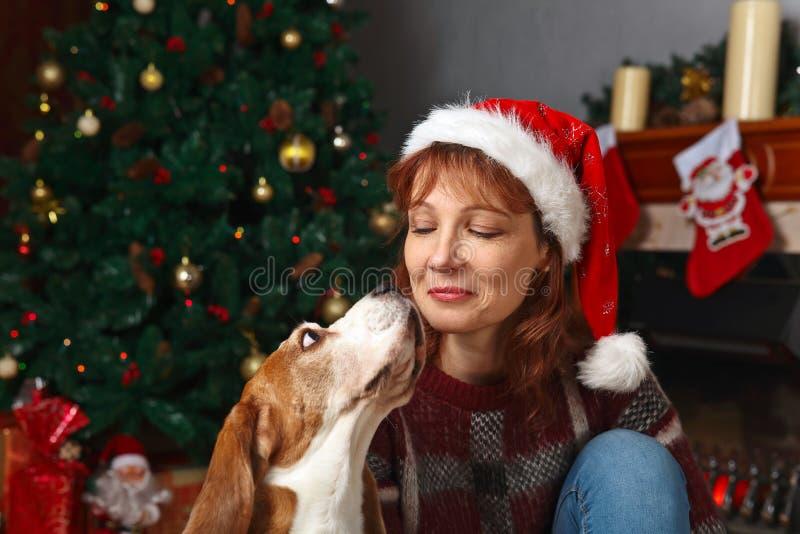 Vrouw met hond in de ruimte met Kerstmisdecoratie stock afbeeldingen