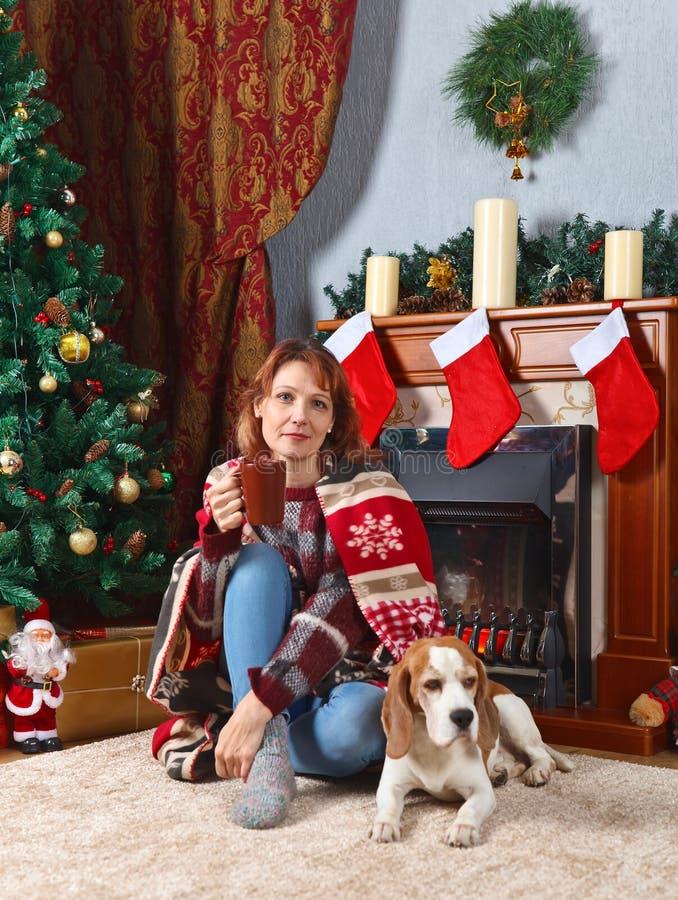 Vrouw met hond in de ruimte met Kerstmisdecoratie stock afbeelding