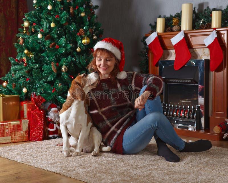 Vrouw met hond in de ruimte met Kerstmisdecoratie stock fotografie