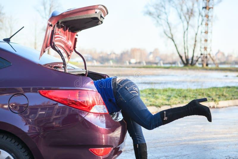 Vrouw met hoofd die in de geopende autoboomstam krijgen