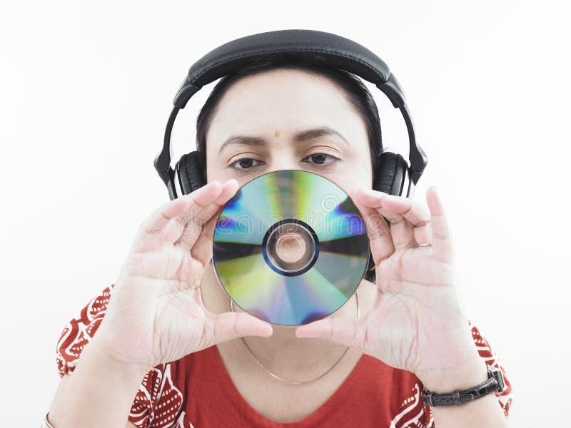 Vrouw met hoofdtelefoons en CD stock afbeelding