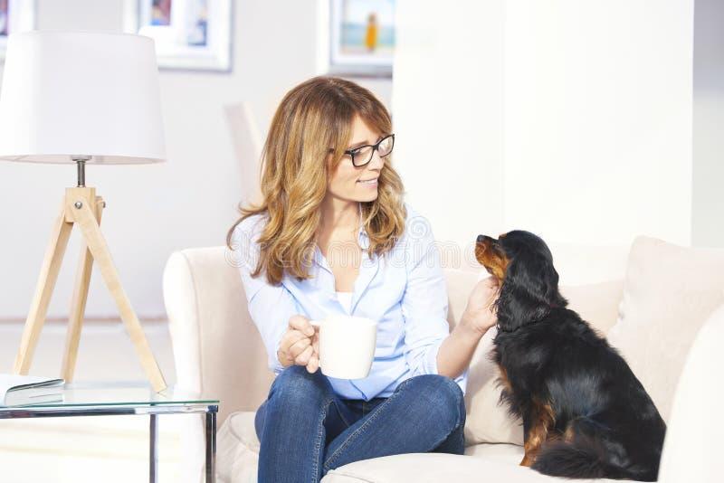 Vrouw met huisdierenhond thuis royalty-vrije stock afbeelding