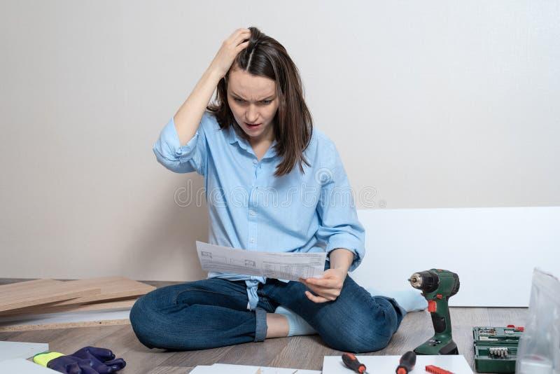Vrouw met instructies voor de assemblage van meubilairzitting op de vloer stock foto's