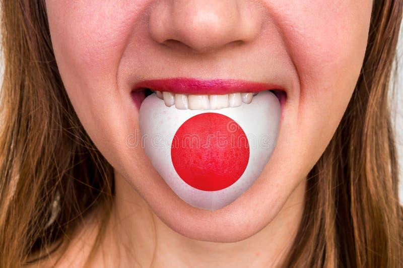Vrouw met Japanse vlag op de tong stock afbeelding