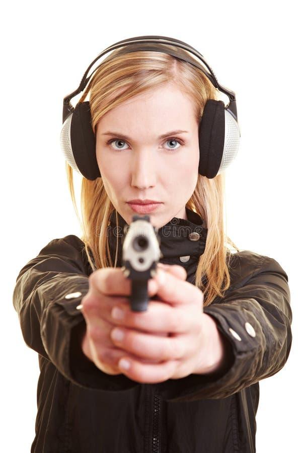 Vrouw met kanon en oorbescherming stock afbeelding