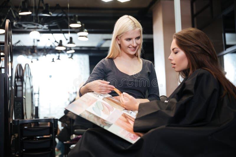 Vrouw met kapper die haarkleur kiezen van palet bij salon royalty-vrije stock foto