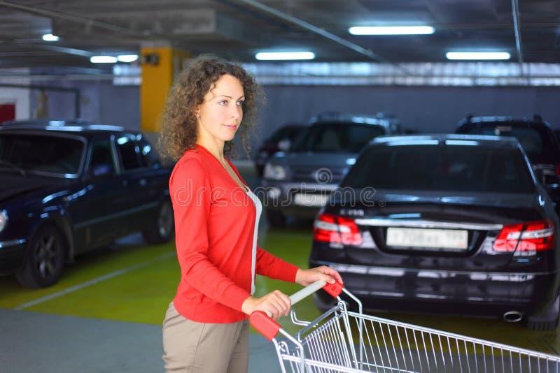 Vrouw met kar die zich in parkeren bevindt stock afbeeldingen