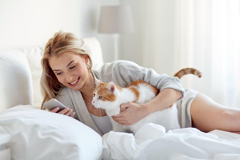 Vrouw met kat en smartphone in bed thuis stock fotografie