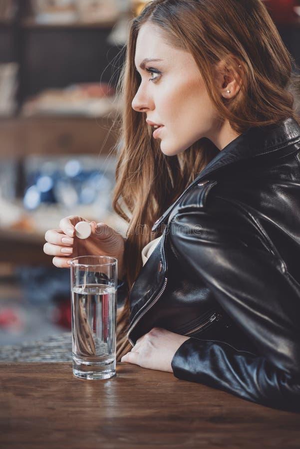 Vrouw met kater met geneesmiddelen in slordige ruimte stock foto's