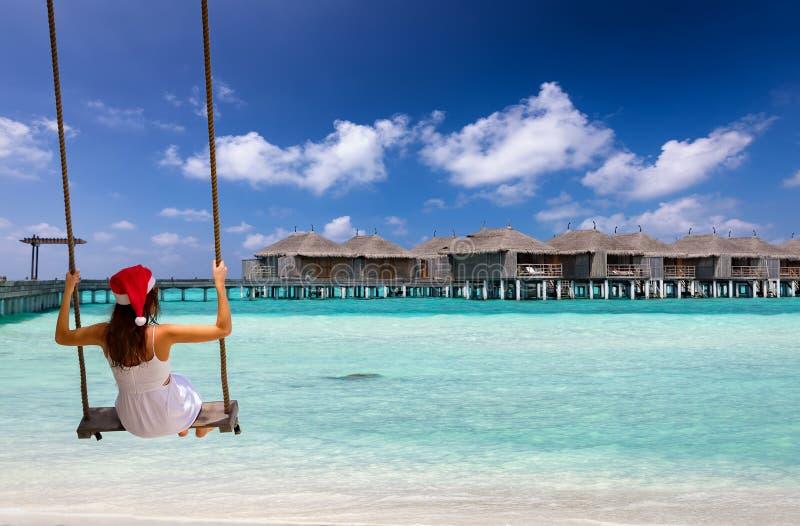 Vrouw met Kerstmishoed op een schommeling voor een tropisch strand stock fotografie