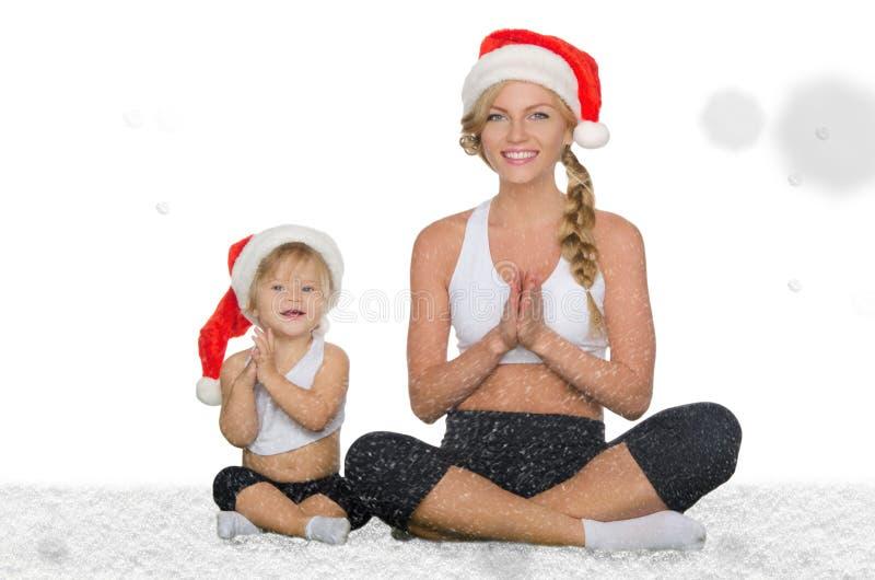 Vrouw met kind die yoga doen onder dalende sneeuw royalty-vrije stock fotografie