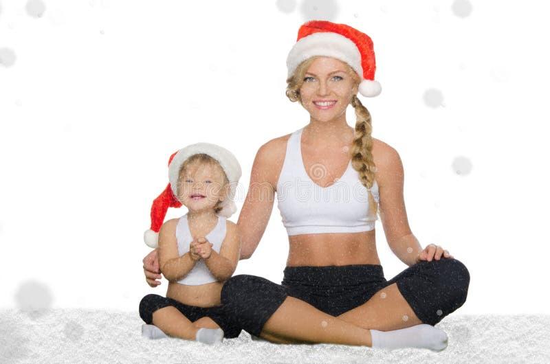 Vrouw met kind die yoga in Kerstmishoeden doen stock foto's