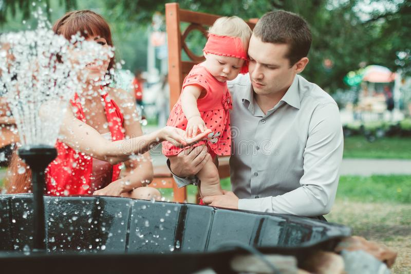 Vrouw met kind het spelen tegen plonsen van water royalty-vrije stock afbeeldingen