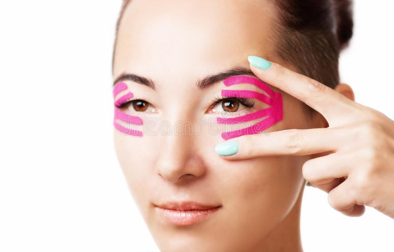 Vrouw met kinesiologieband op ooglid stock afbeelding