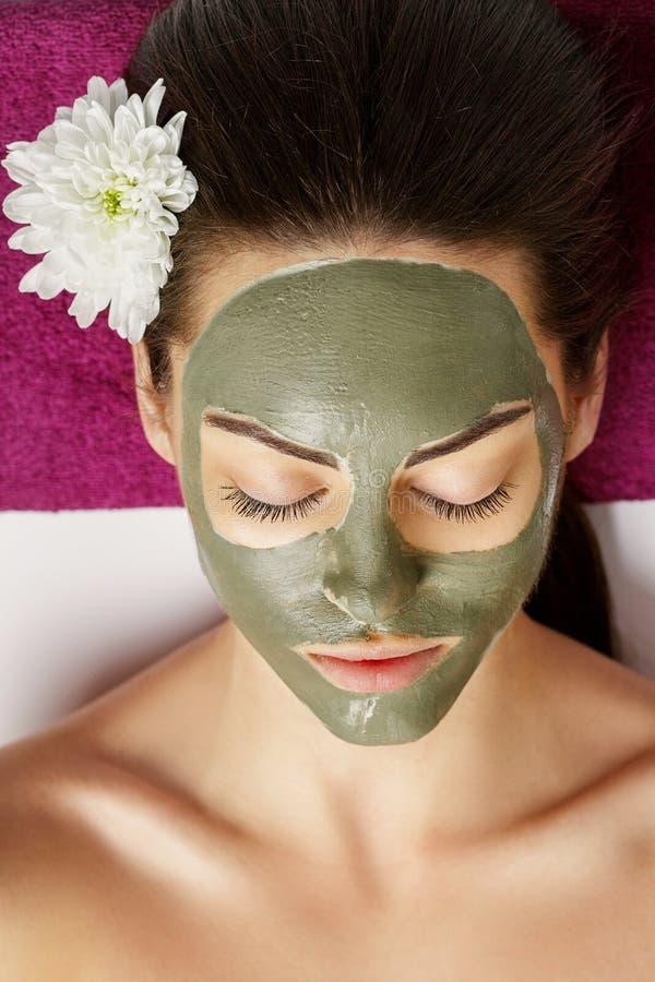 Vrouw met klei gezichtsmasker in beauty spa Skincare Het concept van de schoonheid Gezichtsbehandeling cosmetology r stock fotografie