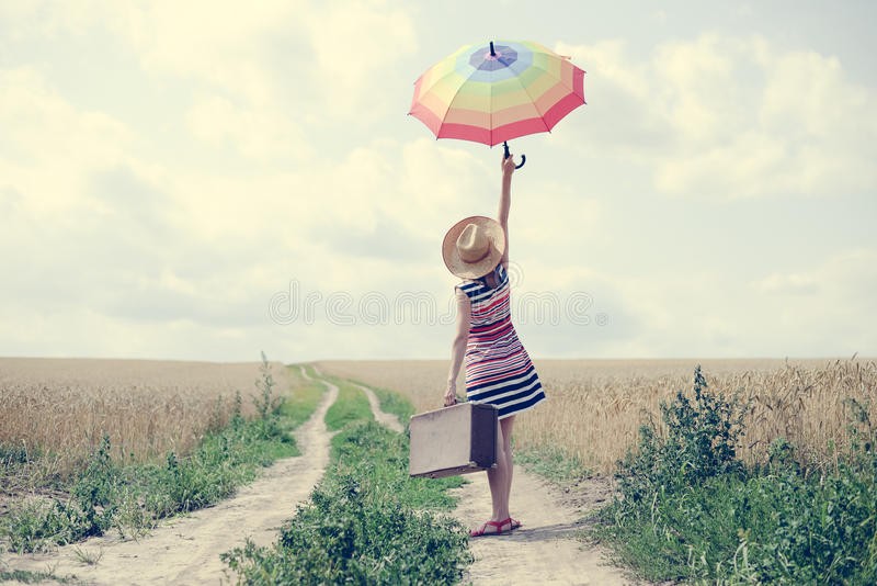 Vrouw met koffer en paraplu die zich op weg bevinden royalty-vrije stock fotografie