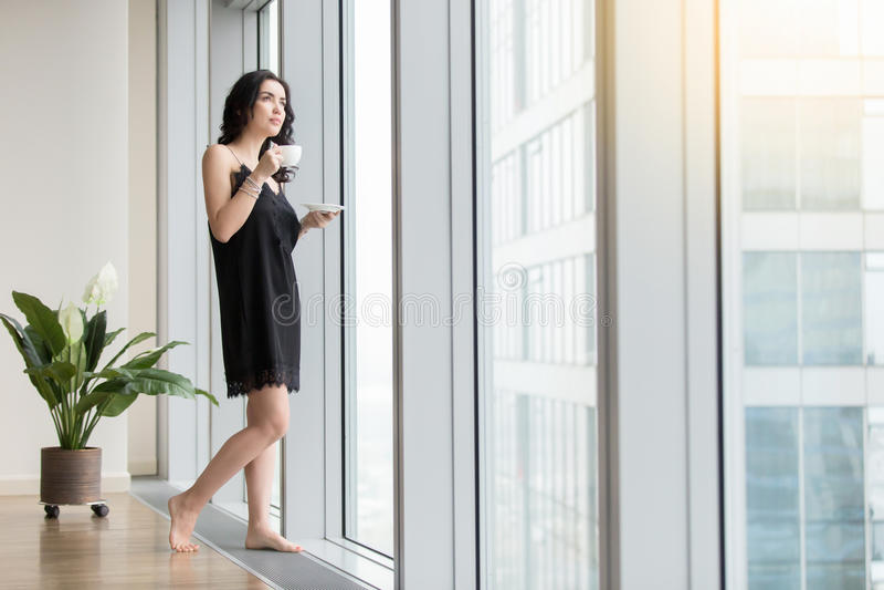 Vrouw met koffie dichtbij het venster royalty-vrije stock foto's