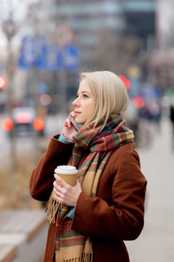 Vrouw met kop koffie met mobiel bellen royalty-vrije stock foto