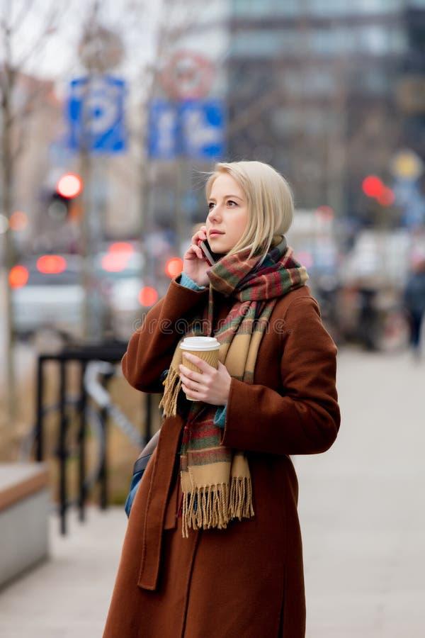 Vrouw met kop koffie met mobiel bellen stock afbeeldingen