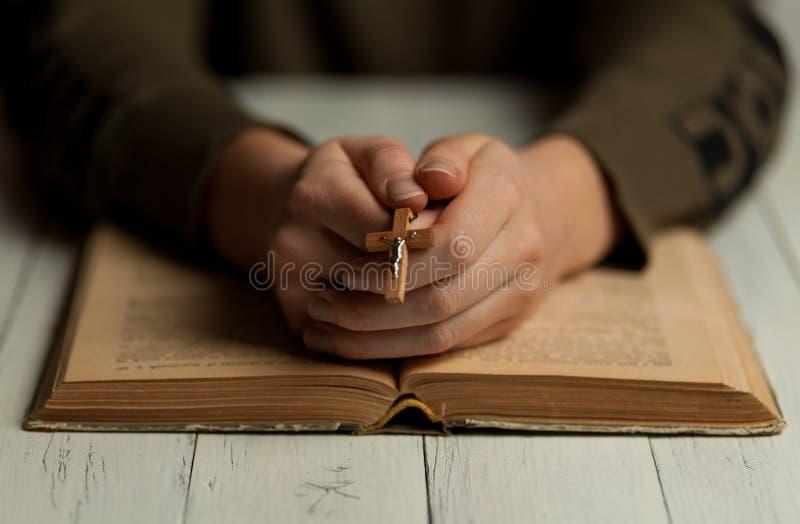 Vrouw met kruisbeeld in haar handen leest de Bijbel. Het leren van het evangelie en het katholicisme royalty-vrije stock fotografie