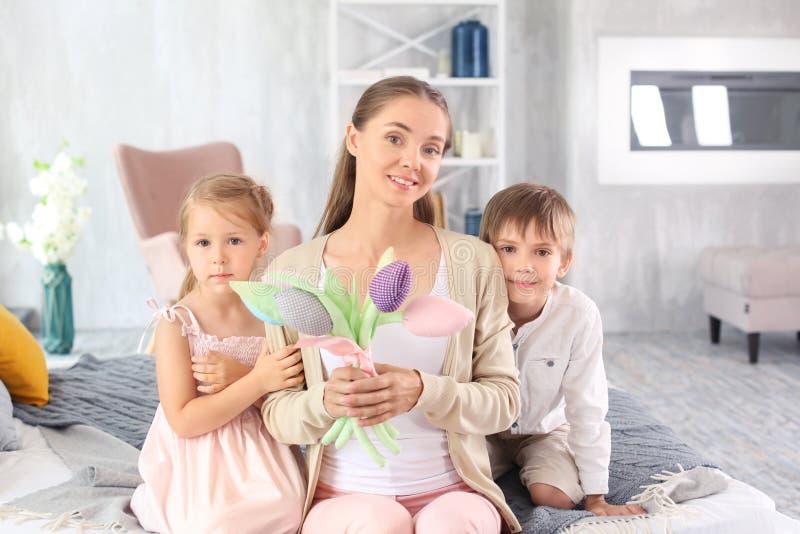 Vrouw met kunstbloemen van haar kinderen voor Moederdag thuis worden ontvangen die stock fotografie