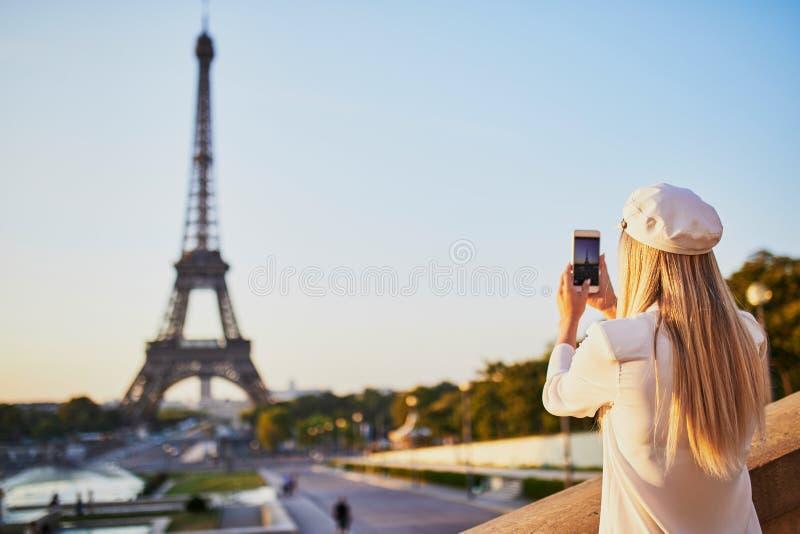 Vrouw met lang blond haar die foto van de toren van Eiffel nemen stock foto