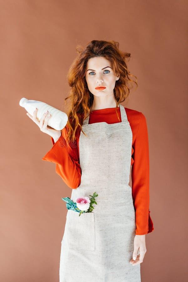 Vrouw met lang rood haar in de melkfles van de schortholding stock afbeelding