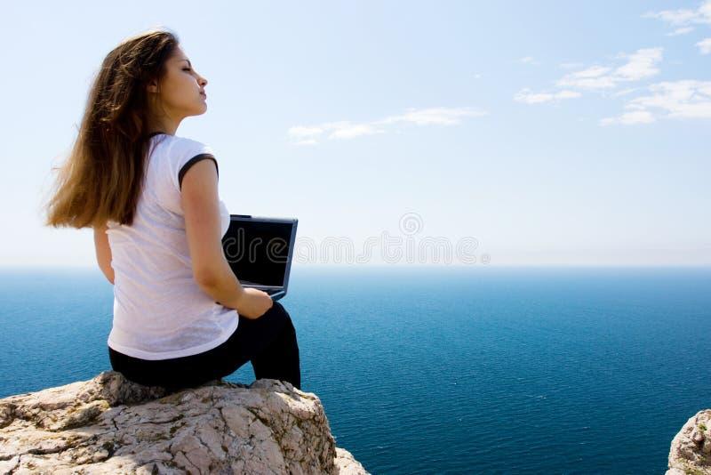 Vrouw met laptop en overzees stock fotografie