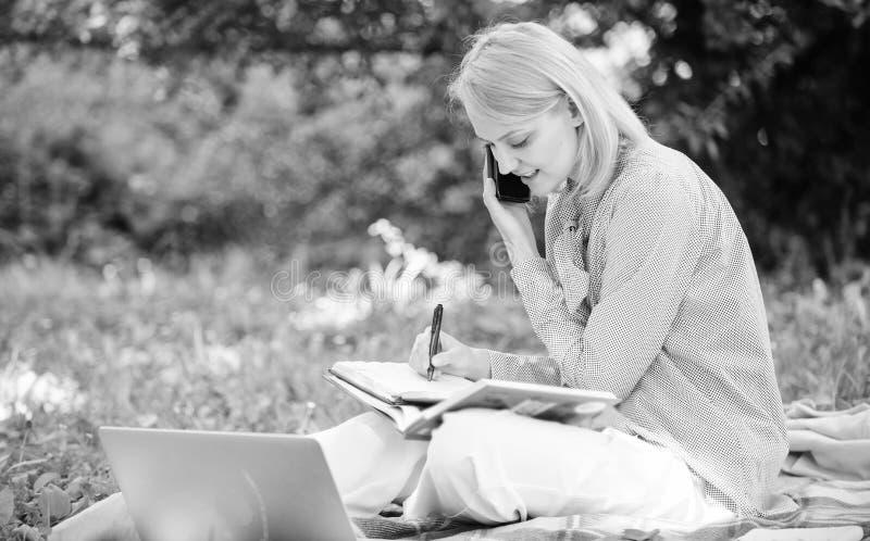 Vrouw met laptop en smartphone die in openlucht werken De moderne technologie van het meisjesgebruik voor zaken Digitale gebruiks royalty-vrije stock foto