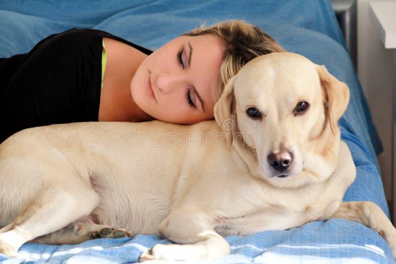 Vrouw met leuke honden thuis Knap meisje die en met haar hond in bed in slaapkamer rusten slapen Eigenaar en hondslaap in bank stock afbeelding