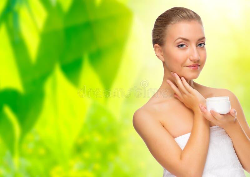 Vrouw met lichaamscrème op bloemenachtergrond royalty-vrije stock afbeelding