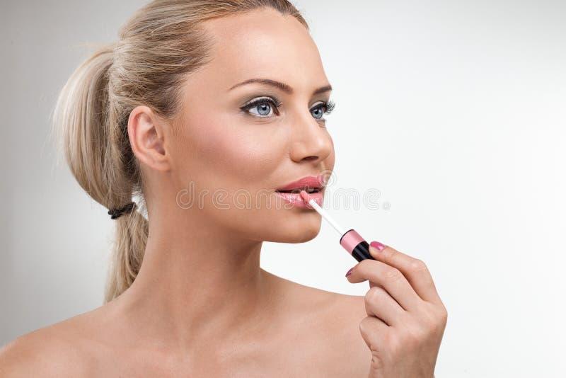 Vrouw met lipgloss stock afbeelding