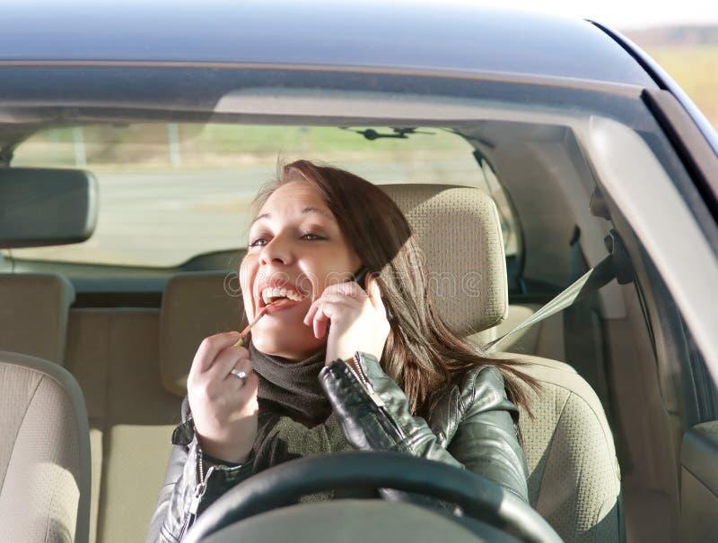 Vrouw met lippenstift en celtelefoon in de auto royalty-vrije stock foto
