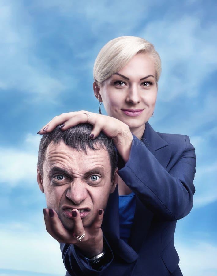 Vrouw met man hoofd in haar hand royalty-vrije stock afbeeldingen