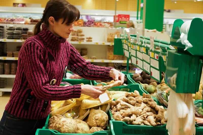 Vrouw met mand het kopen gember bij de kruidenierswinkelopslag De ruimte van het exemplaar royalty-vrije stock afbeelding
