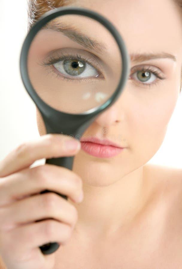 Vrouw met meer magnifier lens op oog stock afbeelding