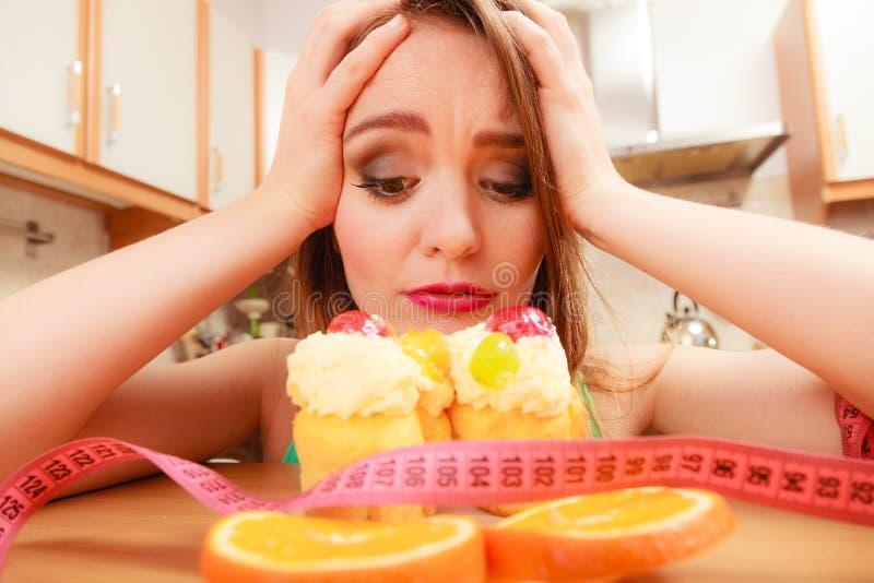 Vrouw met meetlint en cake Dieetdilemma royalty-vrije stock afbeeldingen